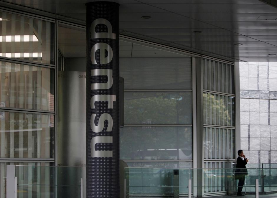 FILE PHOTO: A man speaks on his mobile phone near a logo of Dentsu Co. at the entrance of the company headquarters in Tokyo